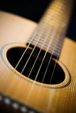 Hand on Guitar Fretboard. Close-up of the fretboard of an electric guitar with a hand out-of-focus in the background Royalty Free Stock Images