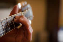 Hand on guitar. Man hand playing acoustic guitar close up Stock Photos
