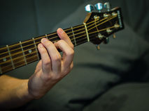 A hand on a guitar neck. F# chord on acoustic guitar Royalty Free Stock Photos