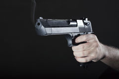 Hand with Gun. Smoking gun after the shot in the hand of man Royalty Free Stock Photography