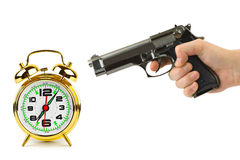 Hand with gun and alarm clock Royalty Free Stock Photos