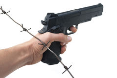 Hand with gun and barbed wire Stock Photo