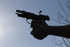 Hand Gun Being Fired with Bullet Being Discharged. A handgun or pistol being shot and fired and showing the bullet being discharged. Silhouette against a blue Stock Photo