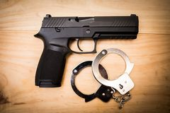 Hand gun with hand cuffs on wooden surface. Concept Royalty Free Stock Photography