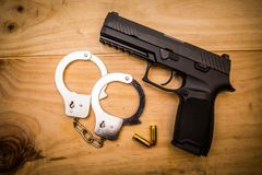 Hand gun with hand cuffs on wooden surface. Concept Stock Photos