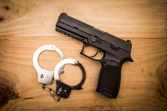 Hand gun with hand cuffs on wooden surface. Concept Royalty Free Stock Photos