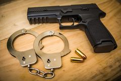Hand gun with hand cuffs on wooden surface. Concept Royalty Free Stock Images