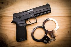 Hand gun with hand cuffs on wooden surface. Concept Royalty Free Stock Photo