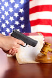 Hand with gun and judges gavel - Vertical Stock Image