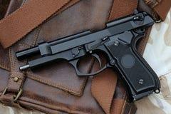 Hand gun, pistol. Semi-automatic handgun and tactical flashlight lying over a Leather handbag, 9mm pistol stock image
