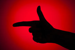 Hand gun. Silhouette of a hand simulating a gun on a red background Royalty Free Stock Image