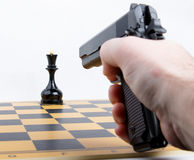 Hand with gun took aim at chess piece Stock Photos