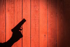 Hand with a gun on a wooden fence Stock Photos