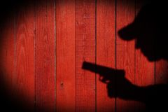 Hand with a gun on a wooden fence Royalty Free Stock Image