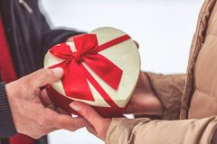 Hand of guy giving his girlfriend Christmas present close up royalty free stock photo