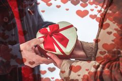 Hand of guy giving his girlfriend valentines present stock image