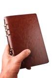 Hand hält ein ledernes Notizbuch an Stockbild