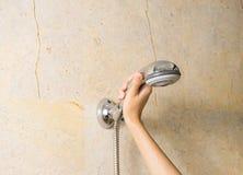 Hand hält eine Dusche auf Marmorhintergrund lizenzfreie stockfotos