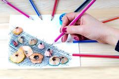Hand hält einen Bleistift Bleistiftspitzerschnitzel auf Tabelle Stockfoto