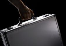 Hand hält Koffer an Lizenzfreie Stockbilder