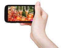 Hand hält Mobiltelefon mit Weihnachtsstillleben Lizenzfreies Stockfoto