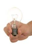Hand hält weißglühende Lampe an Stockfoto