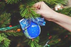 Hand hängt am schönen blauen Ball des Weihnachtsbaums mit Bogen Stockfoto