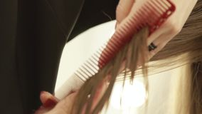 Hand haircutter combing strand hair and cutting with hairdressing scissors in beauty salon. Close up woman hairdressing stock video footage