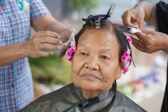 Hand of a hairstylist doing a perm rolling hair of senior woman Royalty Free Stock Photos