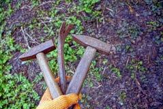 In hand hamers en spijkers stock foto