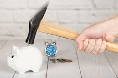 A hand with hammer breaking the money box. Alarm clock on background royalty free stock photo