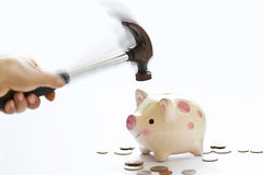 Hand with hammer breaking piggy bank on white background, soft a Royalty Free Stock Image