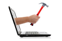 Hand with hammer. Comes from laptop screen on the white background stock photos