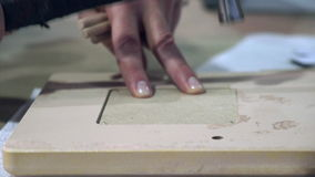 Hand hammers a nail into the frame.