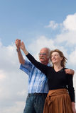 Hand in hand. Joyful couple standing hand in hand against cloudy sky Stock Photo