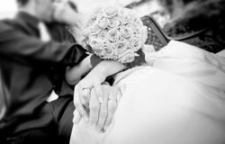 Hand in hand. Newlyweds in black and white holding hands and kissing Royalty Free Stock Image