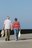 Hand In Hand. Rear view of an elderly couple walking together and holding hands along a seaside promenade. Set against a blue sky Royalty Free Stock Photo