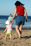 Hand in Hand. Mother and daughter walking on the beach holding hands royalty free stock photos