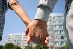Hand in Hand. Couple holding hands with apartments in the background Royalty Free Stock Photos