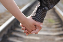 Hand by hand... Guy and girl walking hand by hand along railroad stock photography