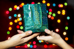 Hand in hand is giving the gift. Of an adult child  on the background of colorful bright Bokeh Royalty Free Stock Photo