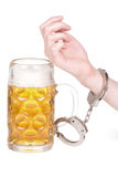 Hand handcuffed to a beer mug Stock Images