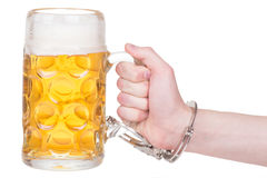 Hand handcuffed to a beer mug Royalty Free Stock Photography