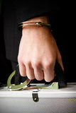 Hand in handcuffs holding money suitcase Stock Photo