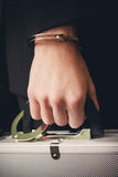 Hand in handcuffs holding money suitcase Royalty Free Stock Image