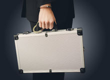 Hand in handcuffs holding money suitcase Stock Photos