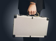 Hand in handcuffs holding money suitcase Stock Image