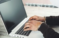 Hand handcuffs on keyboard royalty free stock images