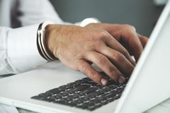 Hand handcuffs on keyboard royalty free stock photography