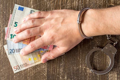Hand in handcuffs is taking Euros Royalty Free Stock Image